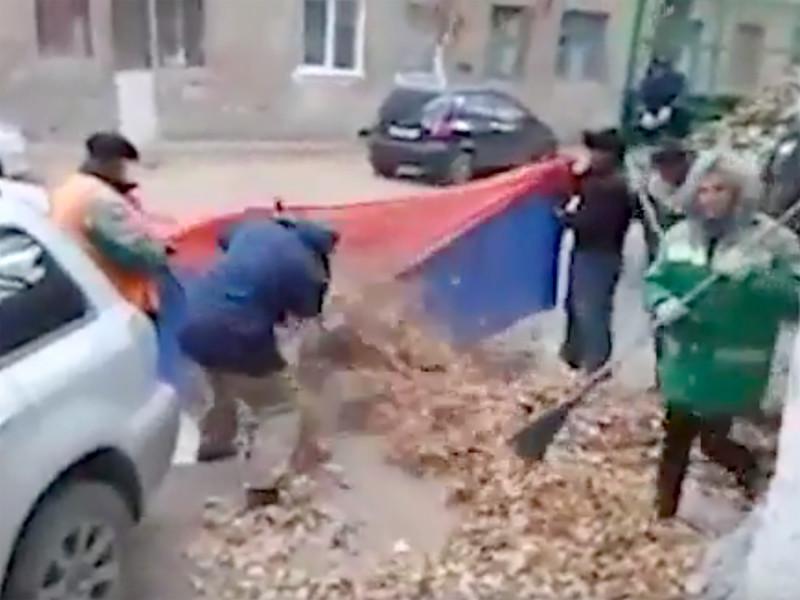 В Тракторозаводском районе Волгограда местные дворники убирают мусор и листву, используя в качестве мешка российский триколор