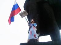 В Новосибирске студентка в ночнушке и с российским флагом приковала себя цепями к памятнику Ленина