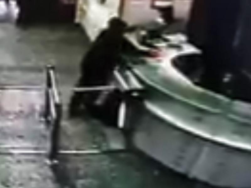 На кадрах мужчина в черной одежде показывает какие-то бумаги сотруднику охраны, после чего распыляет газ из баллончика и проскакивает под турникетом