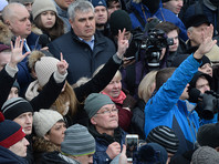Люди показывают на пальцах сколько родственников у них погибло при пожаре в торгово-развлекательном центре «Зимняя вишня» во время митинга на площади Советов у здания администрации в Кемерово