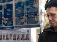 Военнослужащий Черноморского флота рассматривает список кандидатов в президенты РФ перед досрочным голосованием в одном из избирательных участков Севастополя