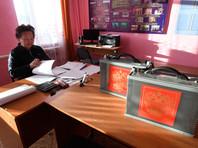 Член участковой избирательной комиссии села Цокто-Хангил подсчитывает бюллетени после проведения досрочного голосования на выборах президента РФ в Забайкальском крае