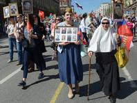 Участники акции несут таблички с изображениями своих родственников, сражавшихся в Великой Отечественной войне, флаги России и Советского Союза. Многие из них одеты в форму советских солдат, пехотинцев, летчиков