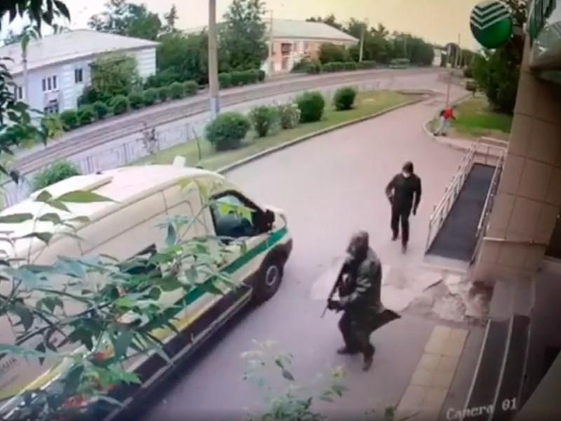 """Двое одетых в черное мужчин с масками на лицах и в капюшонах обстреляли инкассаторов, схватили сумку и скрылись на поджидавших их """"Жигулях"""""""
