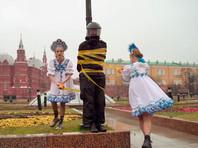 """Участницы группы Pussy Riot провели возле Кремля акцию против полицейского насилия. Мария Алехина и Рита Флорес, одетые в кокошники и русские народные платья, скотчем с надписью """"Осторожно, хрупкое!"""" примотали к столбу на Манежной площади художника Фархада Исрафилли-Гельмана в форме омоновца"""