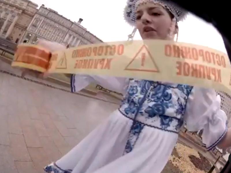 """В конце ноября участницы группы Pussy Riot провели возле Кремля акцию против полицейского насилия. Мария Алехина и Рита Флорес (на фото), одетые в кокошники и русские народные платья, скотчем с надписью """"Осторожно, хрупкое!"""" примотали к столбу на Манежной площади художника Фархада Исрафилли-Гельмана в форме омоновца"""