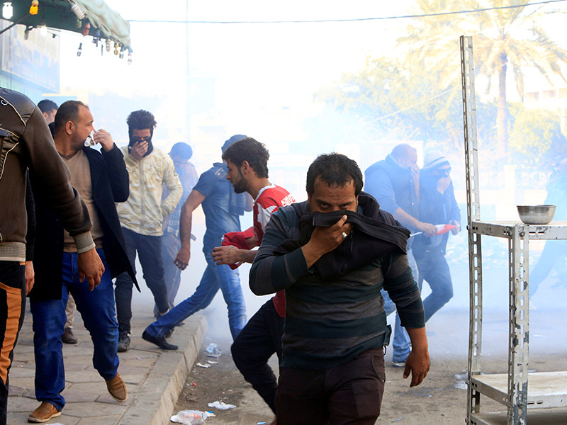 """Сотрудники полиции Ирака применили в субботу слезоточивый газ для разгона тысяч демонстрантов, собравшихся в центре Багдада у охраняемой """"Зеленой зоны"""". По уточненным данным, погибли минимум семь человек, сотни пострадали"""