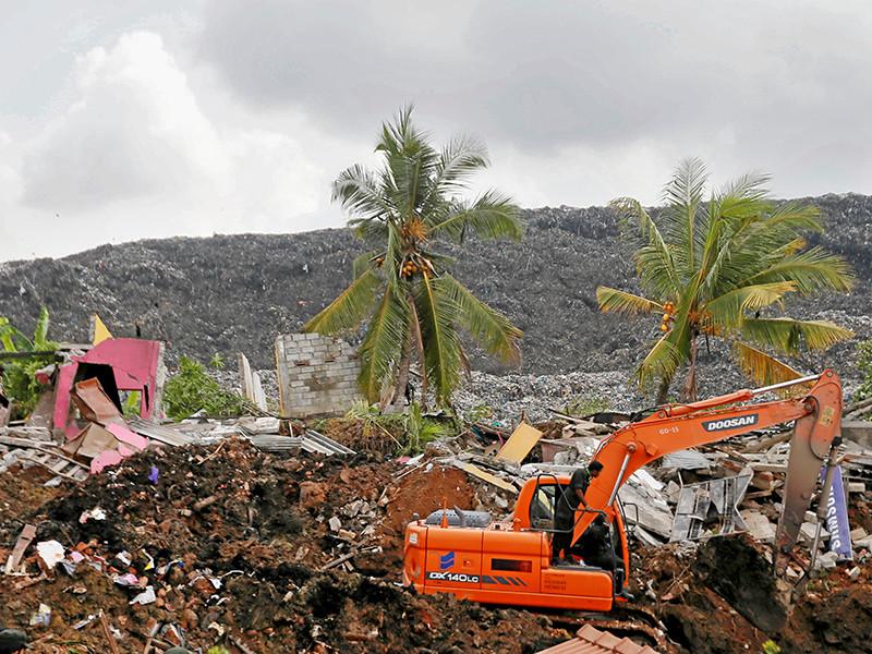 Из-за продолжительных дождей гора мусора на свалке начала смещаться в сторону домов. Reuters оценило высоту горы отходов в 90 метров. В дальнейшем отходы загорелись и рухнули на жилища