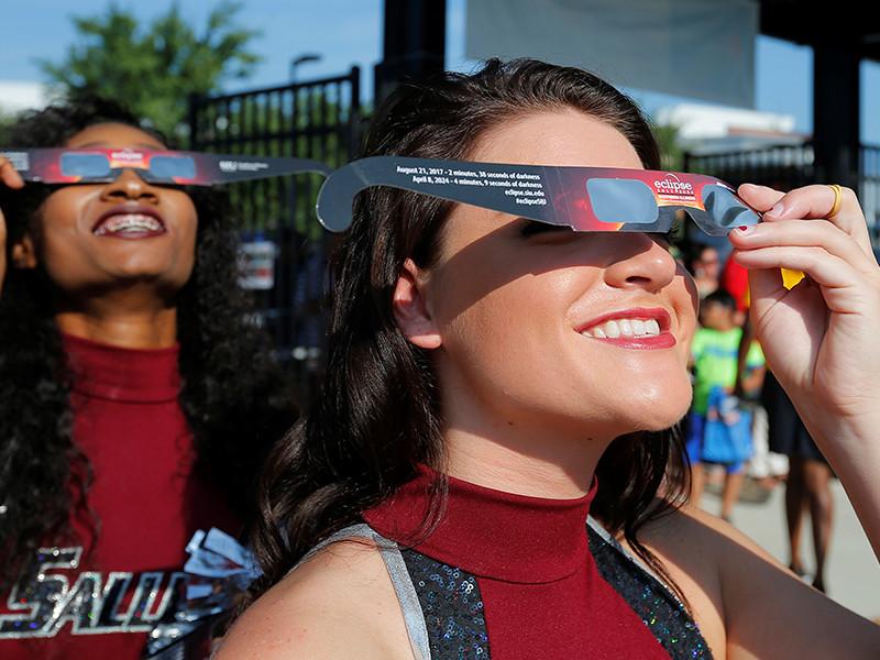 Жители США в телескопы, камеры и в одноразовые защитные очки наблюдают Великое американское затмение