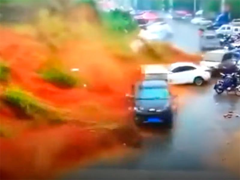 Проливные дожди привели к сходу оползня в уезде Упин в провинции Фуцзянь. Он смел с дороги и накрыл землей машины, а две из них забросил в здание. В результате инцидента погиб один человек