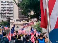"""Участники протестов в Гонконге в воскресенье с пением гимна США и плакатами, призывающими Штаты оказать помощь в """"освобождении"""" города от контроля со стороны Пекина, прошли к зданию американского генерального консульства и передали дипломатам петицию"""