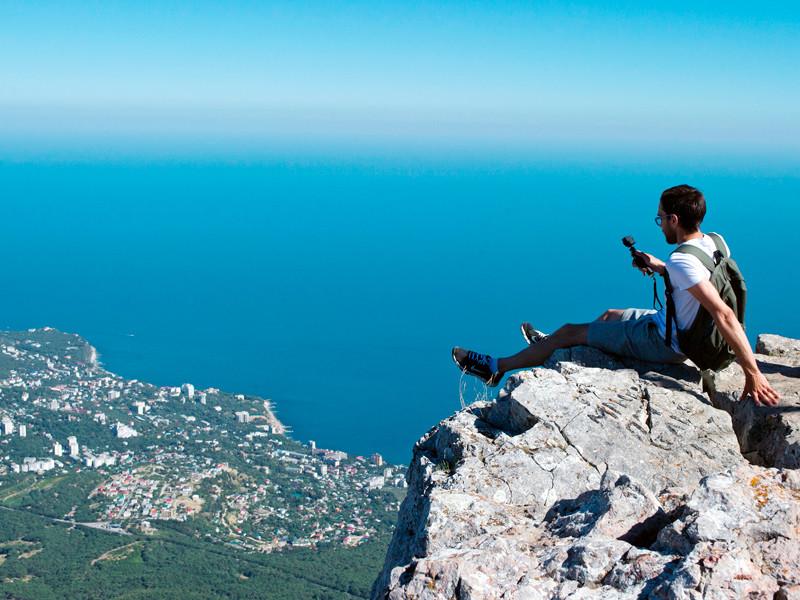 Турист фотографируется на вершине горы Ай-Петри в Крыму