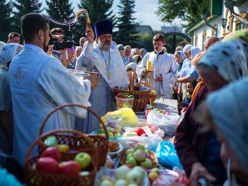 Священнослужитель окропляет святой водой яблоки и фрукты во время богослужения в честь праздника Преображения Господня у собора Воздвижения Креста Господня в Омске